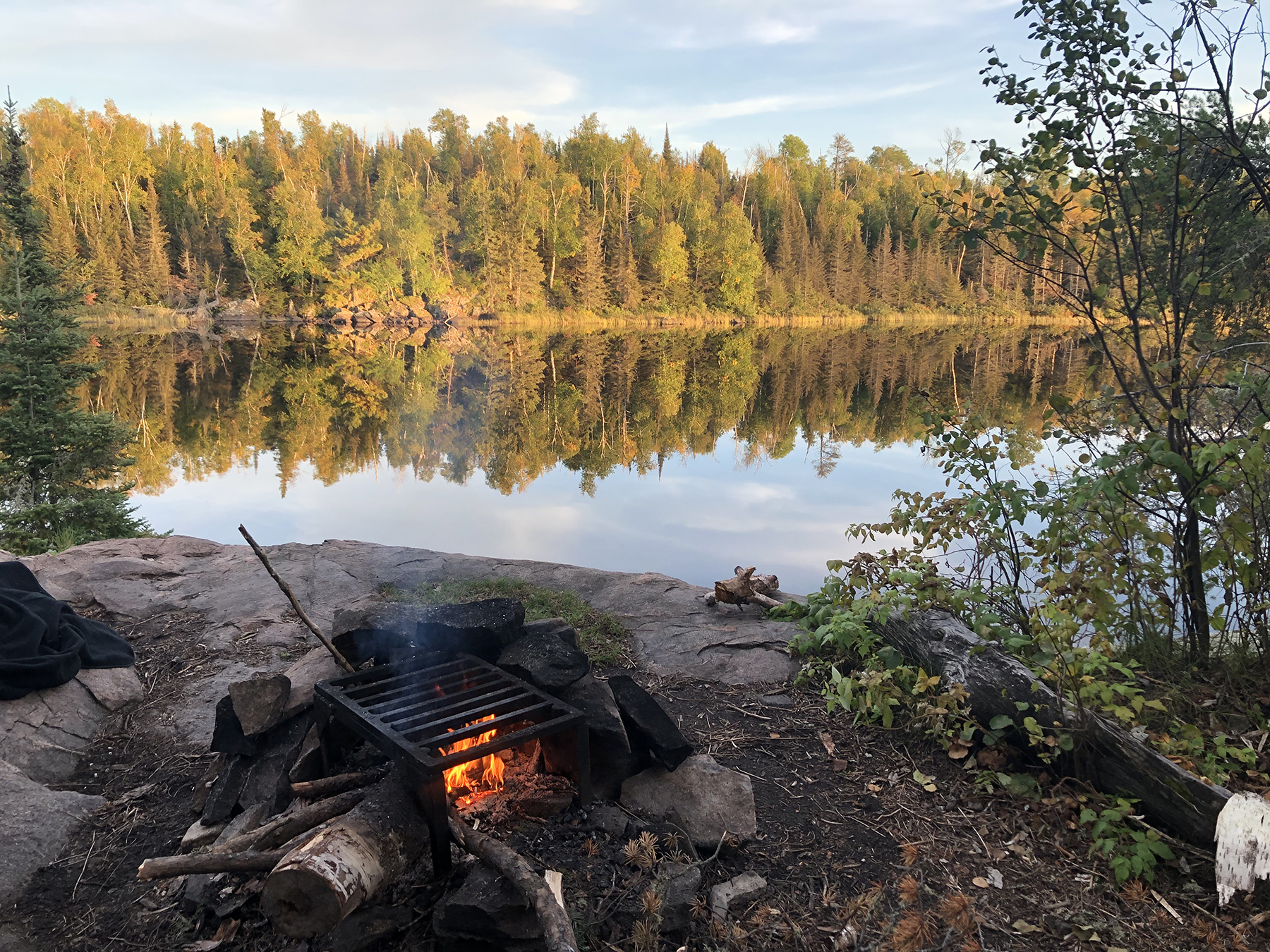 campfire in front of a lake