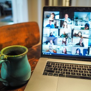 coffee mug in front of a laptop with a video call on the screen