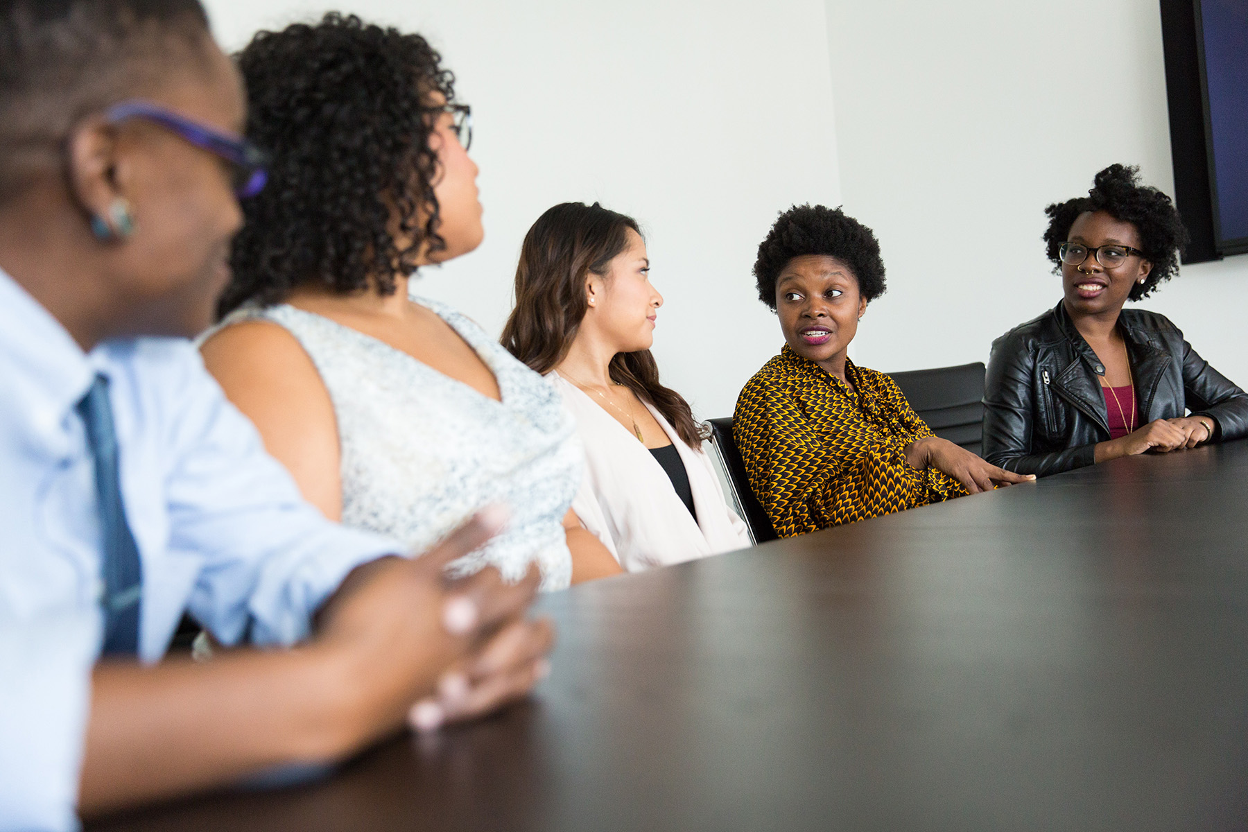 a diverse group of people at a conference room table